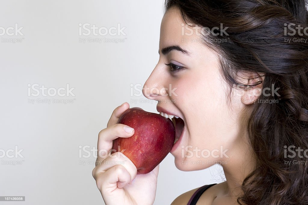 Brunette woman biting into a red apple stock photo