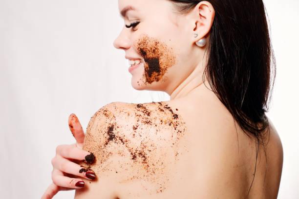 brunette frau reinigt die haut des körpers kaffee peeling - kaffeepeeling stock-fotos und bilder