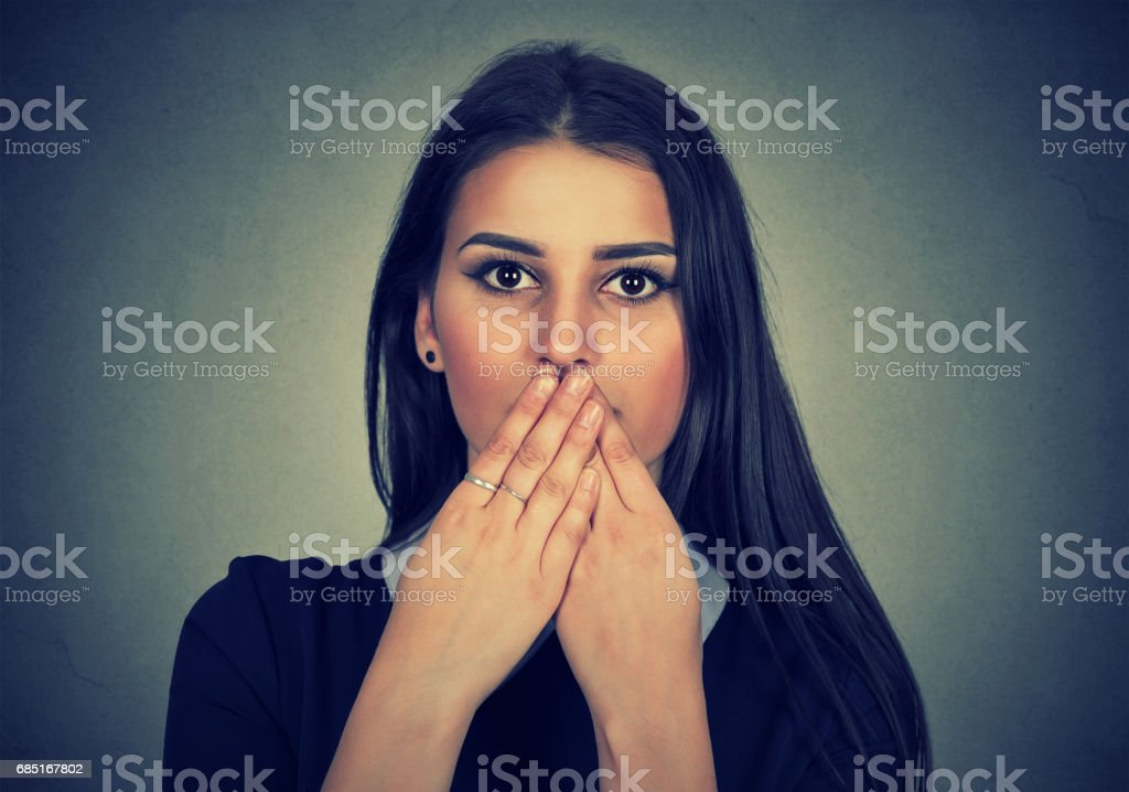 brunette woman covers her mouth with hands royalty-free stock photo