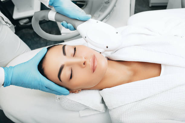 Brunette woman during removes brown spots on face, Beautician using ELOS rejuvenation technology Brunette woman during removes brown spots on face, Beautician using ELOS rejuvenation technology dark spots face stock pictures, royalty-free photos & images
