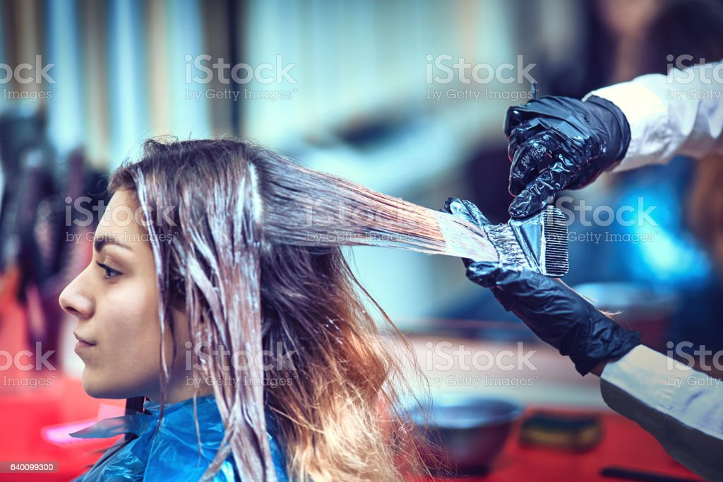 Brunette woman dying her hair at the beauty salon stock photo