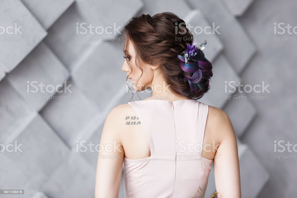Brunette woman hairdo french twist, rear view on gray fashion studio background. Shoulder wit numeric tattoo stock photo