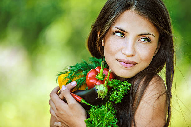 Brunette woman holding vegetables in arms stock photo