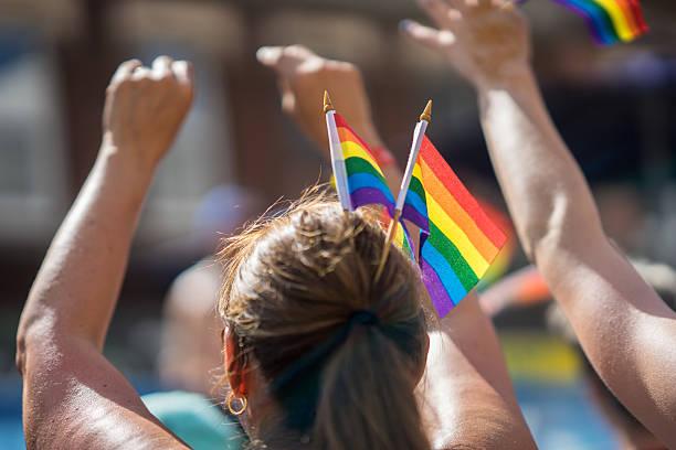 brunette woman in a crowd celebrating pride parade. - modefarben sommer 2016 stock-fotos und bilder