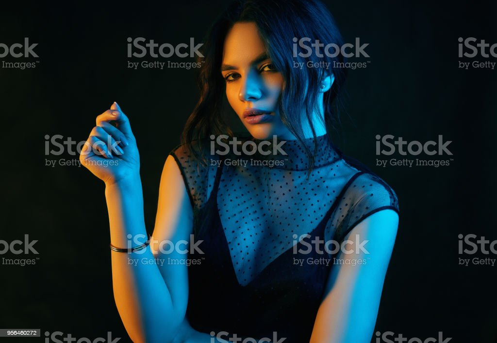 Colorful portrait of a brunette woman in a fashion dress posing on a...