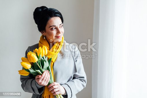 brunette woman in coats with yellow tulips 1