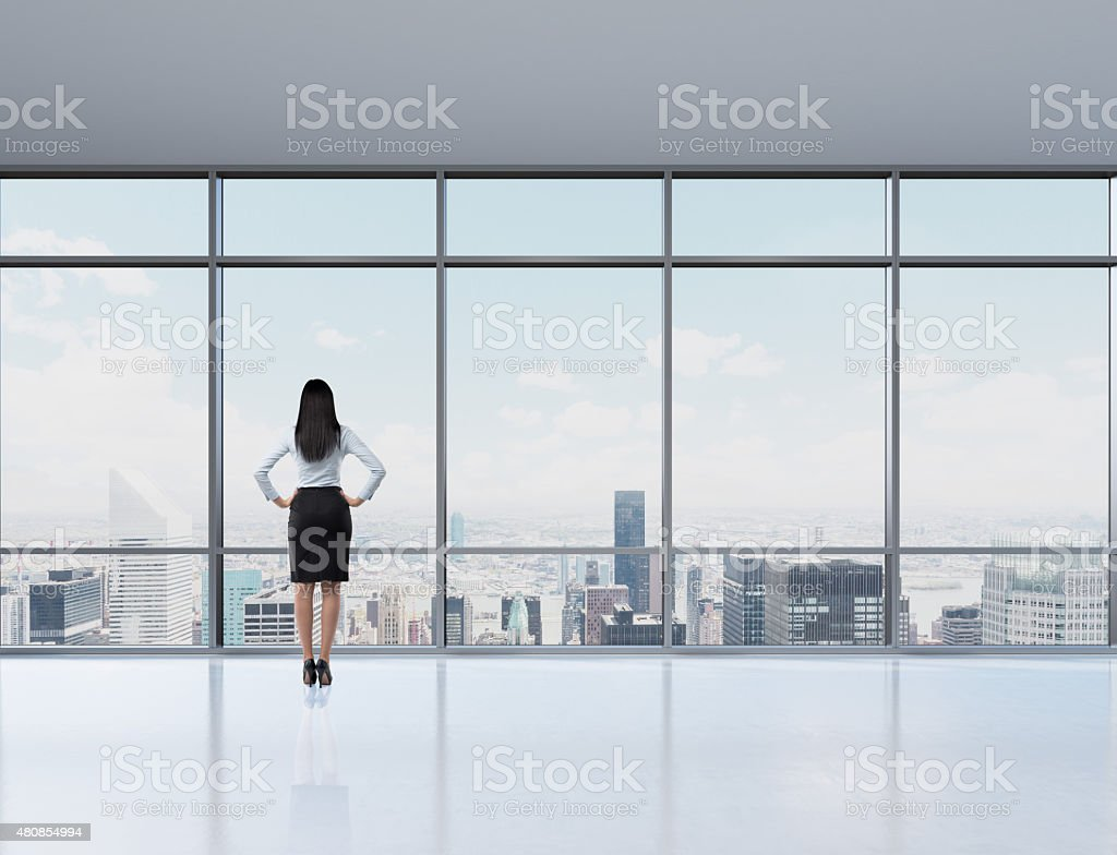 brunette woman in office who looks through the window stock photo