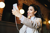 istock Brunette woman in white jacket having dark eyes with long eyelashes, full lips and healthy skin having good mood while resting in cafe listening to different tracks with earphones and making selfie 1169152501
