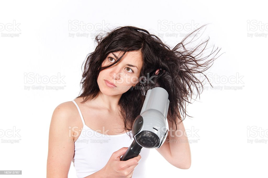 Brunette woman in white tank top blow drying messy hair  royalty-free stock photo