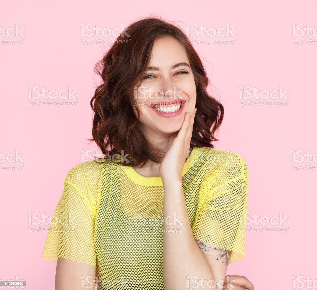 Brunette woman in yellow shirt smiling Young brunette woman wearing sheer yellow t-shirt smiling touching cheek with hand. Women Stock Photo
