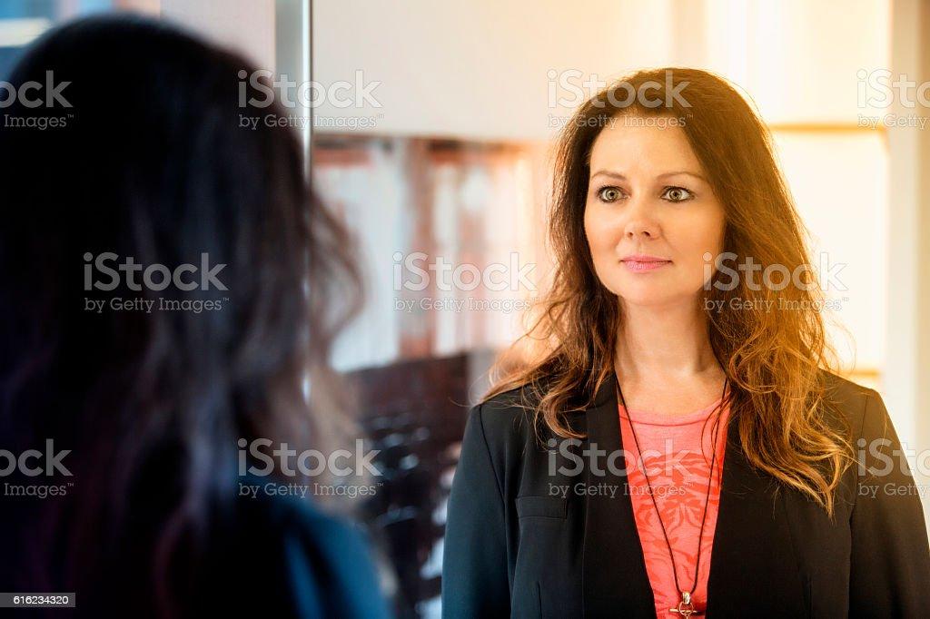 brunette woman looking at herself in mirror – Foto