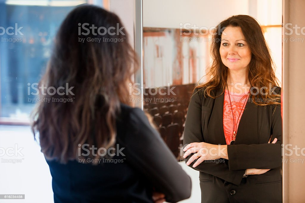 brunette woman looking at herself in mirror stock photo
