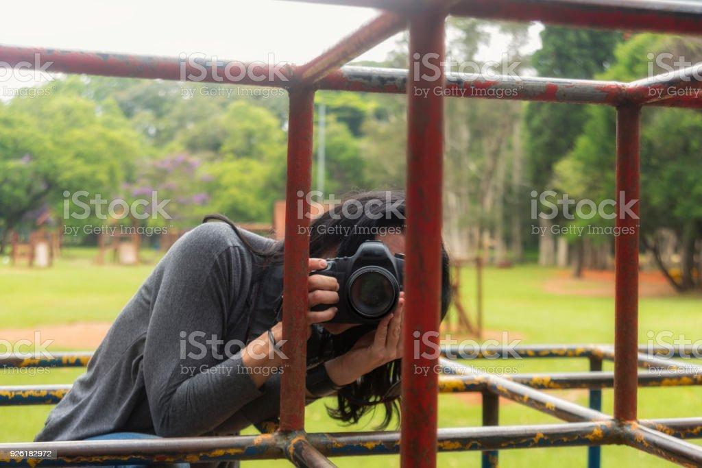 Klettergerüst Erwachsene : Brünette frau fotograf bei einem spielplatzklettergerüst stockfoto