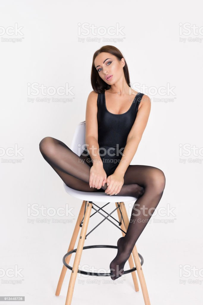 Brunette woman sitting on a bar stool. stock photo