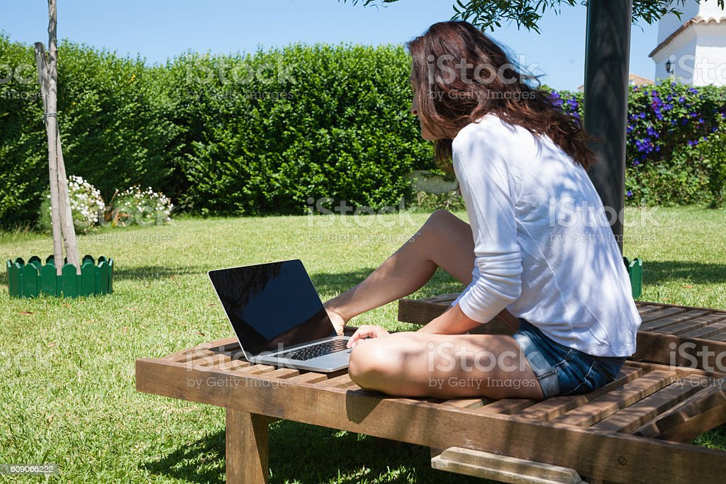 brunette woman using laptop on lounge chair stock photo