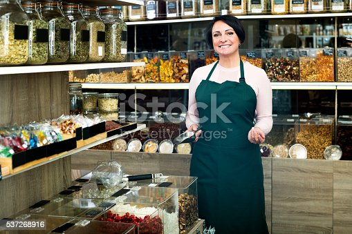 istock Brunette woman wearing apron and selling nuts 537268916