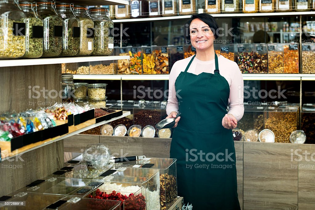 Brunette woman wearing apron and selling nuts stock photo