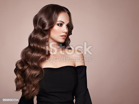 Brunette Girl with Long Healthy and Shiny Curly Hair. Care and Beauty. Beautiful Model Woman with Wavy Hairstyle. Make-Up and Black Dress