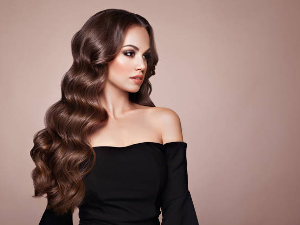 Brunette woman with curly hair Brunette Girl with Long Healthy and Shiny Curly Hair. Care and Beauty. Beautiful Model Woman with Wavy Hairstyle. Make-Up and Black Dress long hair stock pictures, royalty-free photos & images