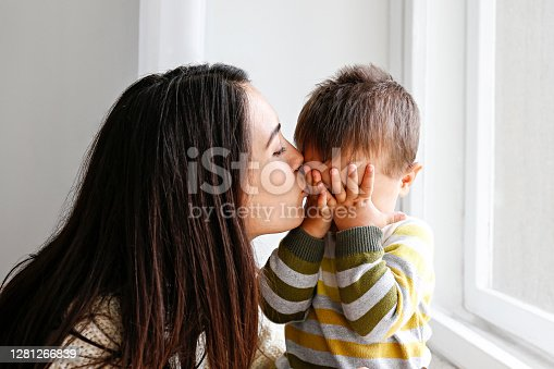 Portrait of young mother kissing her little son in forehead at home. Beautiful female with straight brunette hair playing with child at living room. Close up, copy space, background.