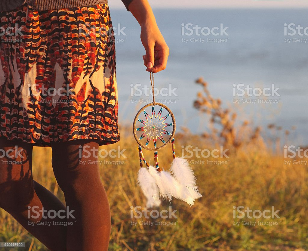 Brunette woman with long hair holding dream catcher - Photo