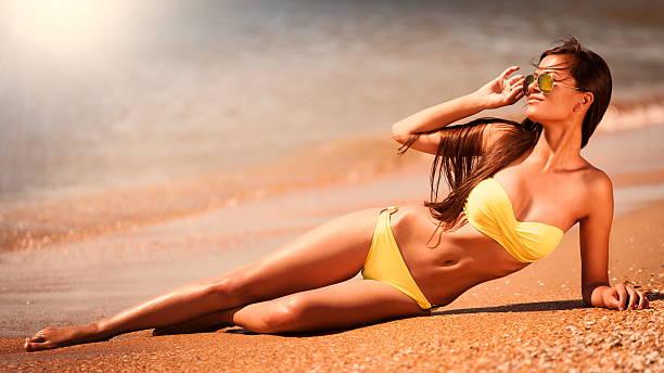 brunette mulher Biquíni amarelo mar - foto de acervo