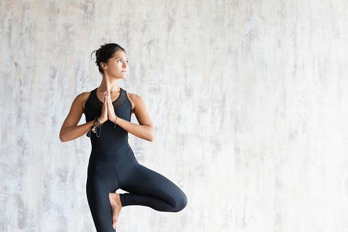 Brunette woman yoga instructor doing vrikshasana