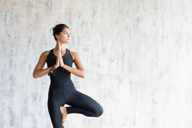 brunette femme instructeur de yoga faisant vrikshasana - yoga photos et images de collection