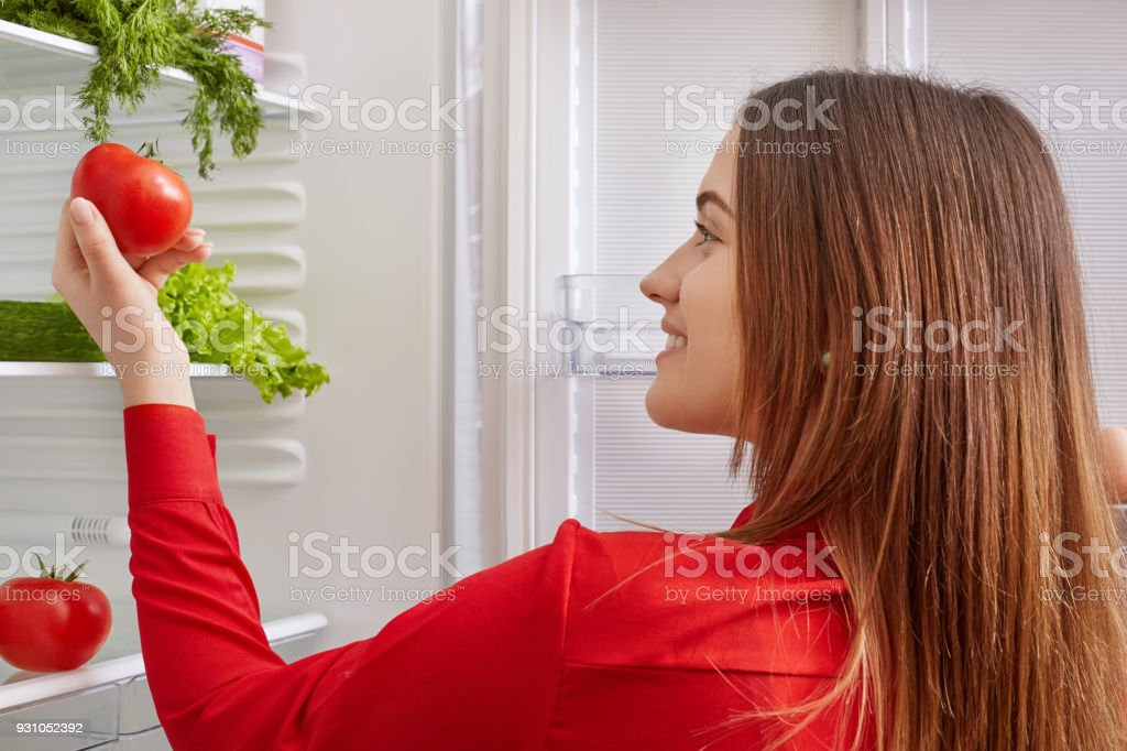 Brunette young female holds ripe tomatoes, stands near opened fridge, going to make healthy fresh vegeterian salad. Back view of housewife chooses necessary products for cooking tasty dinner stock photo