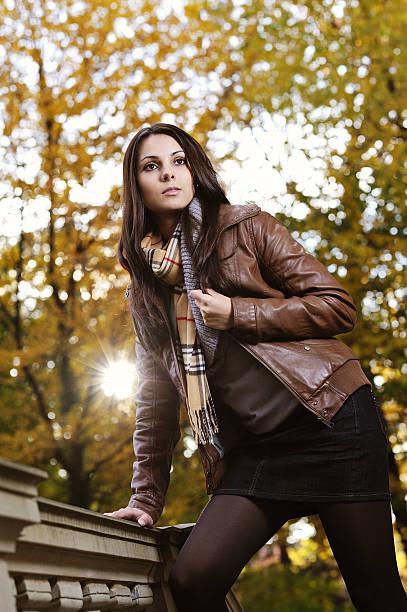 brunette junge frau herbst-outfit vor bäumen und sonnenuntergang sonne - damen rock braun stock-fotos und bilder