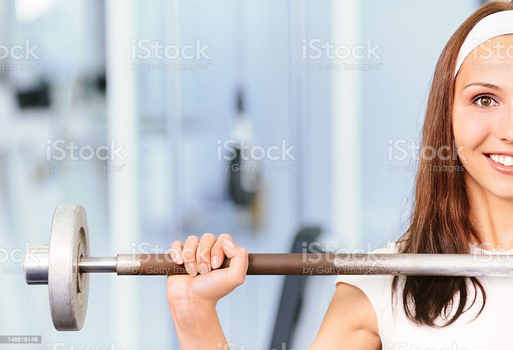 A brunette young woman lifting a barbell and smiling royalty-free stock photo
