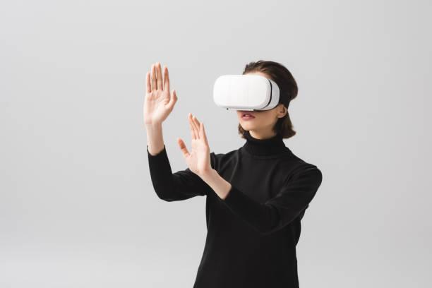 brünette junge Frau trägt Virtual-Reality-Headset, während gestikulieren isoliert auf grau – Foto
