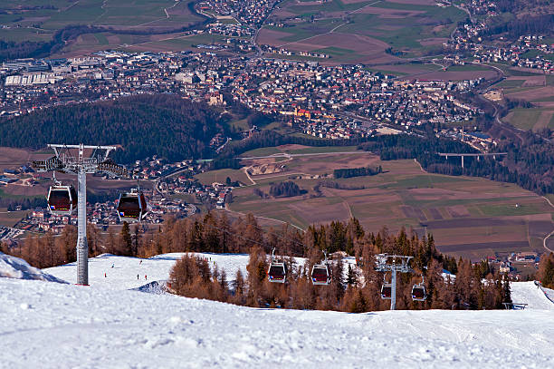 Brunico viewed from Plan de Corones Ski slope and cable car in Dolomites, Italy - Plan de Corones - Kronplatz and Brunico - Brunick town in spring bruneck stock pictures, royalty-free photos & images