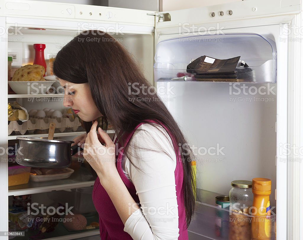 Brunnette woman holding foul food near refrigerator stock photo