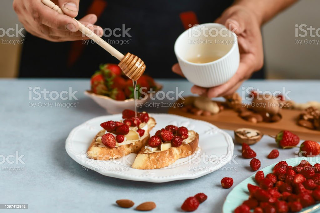 bruschetta cooking by chef hand. Sweet sandwiches with strawberries, cheese, camembert, brie, nuts and honey on light background. Authentic lifestyle image stock photo