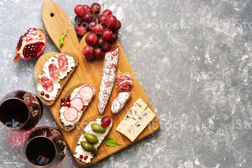 Bruschetta lub autentyczne tradycyjne hiszpańskie tapas, czerwone wino i winogrona na szarym tle. Widok z góry, płaski leżał. - Zbiór zdjęć royalty-free (Znad głowy)