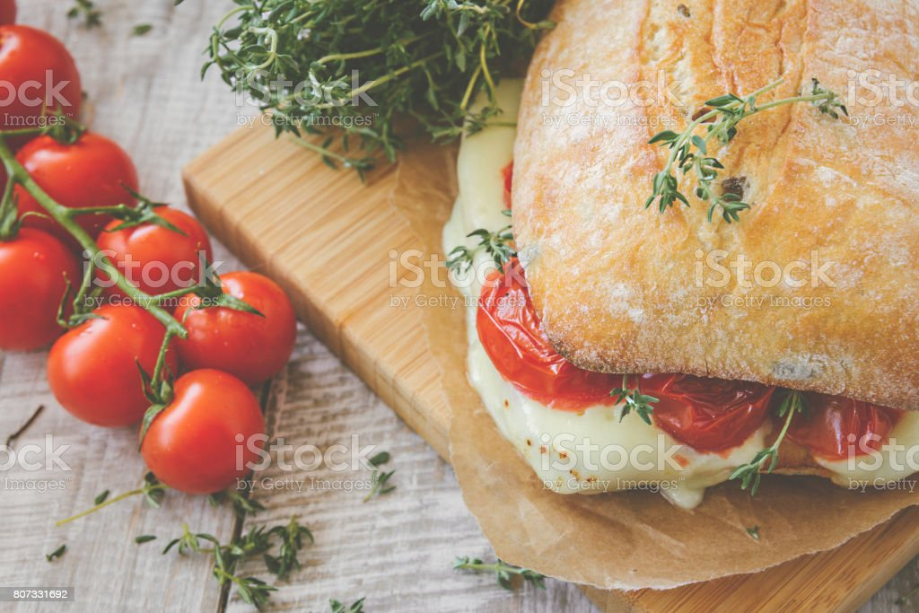 Bruschetta sandwich with tomatoes, herbs and oil on toasted garlic cheese bread. Toned. stock photo