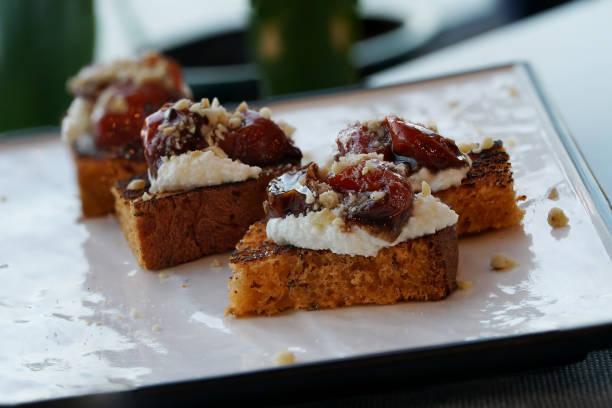 Bruschetta, rebanadas tostadas de pan con queso feta, tomates secos, sobre un plato blanco. - foto de stock