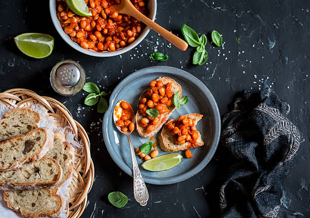 Bruschetta with beans in tomato sauce. Delicious vegetarian appetizer stock photo