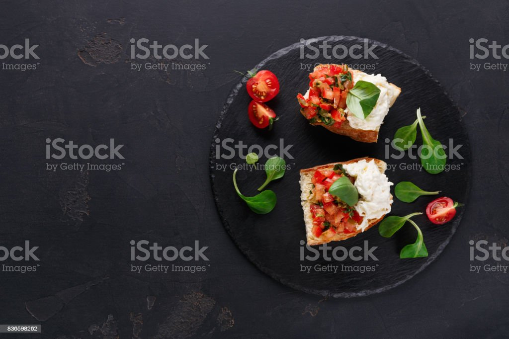 Bruschetta with cheese and vegetables on black background – zdjęcie