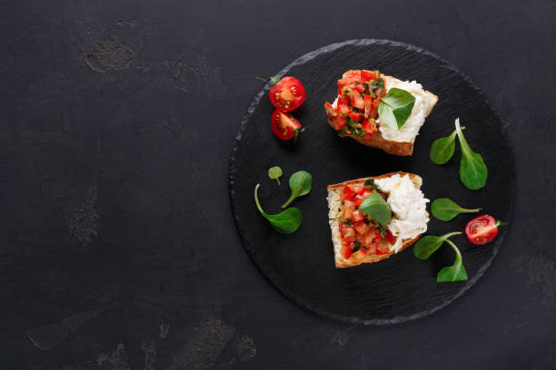 Bruschetta with cheese and vegetables on black background - foto stock