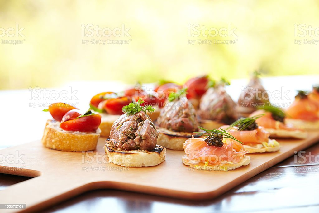 Bruschetta with cheese, tomatoes, foie gras, and wild salmon royalty-free stock photo