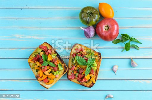 istock Bruschetta with chopped tomatoes and basil over wooden turquoise table 497125678