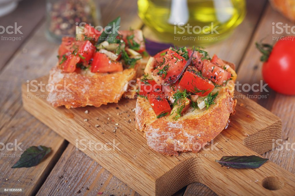 Bruschetta with chopped tomatoes, basil and herbs on grilled crusty bread. стоковое фото