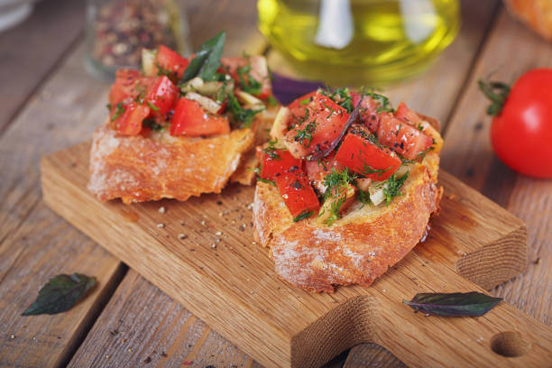 Bruschetta with chopped tomatoes, basil and herbs on grilled crusty bread. - foto stock