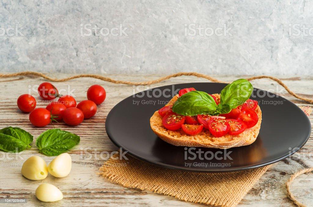 Bruschetta with fresh tomato, basil and garlic on black dish - foto stock