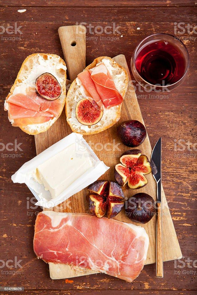 bruschetta with prosciutto ham & figs with white cheese. stock photo