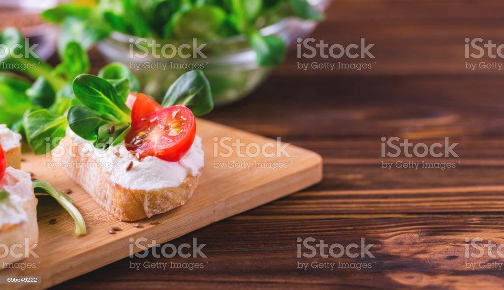 Bruschetta mit Ricotta, Spinat, Feldsalat und Cherry-Tomaten – Foto