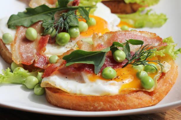 bruschetta mit rucola, chrispy speck, grüne erbse und pochiertem ei auf weißem teller serviert - englischer erbsen salat stock-fotos und bilder
