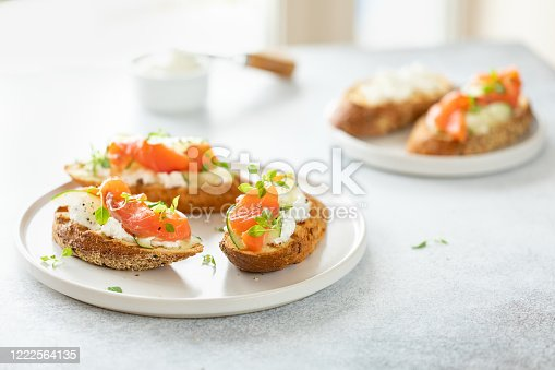 Bruschetta with salmon, curd cheese and cucumber on toast in high key style on white background.